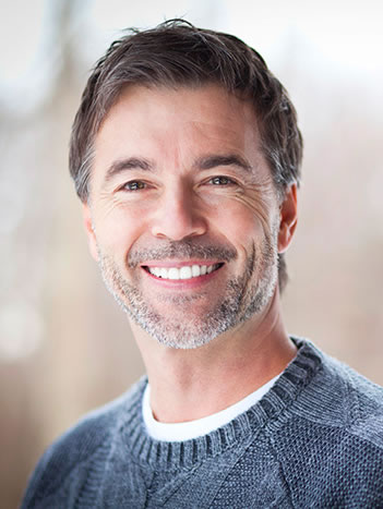 A man who has undergone Full Mouth Reconstruction and other restorative dental procedures for a beautiful smile