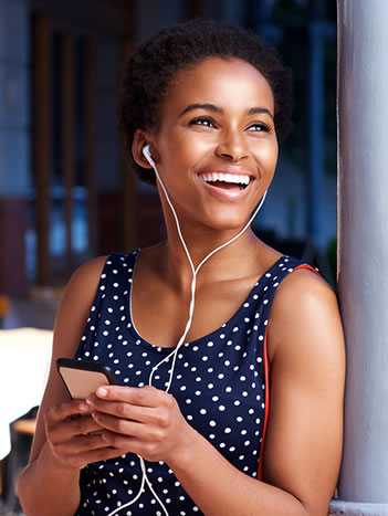 woman listening to music with an even, white smile from veneers