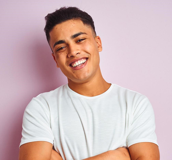 smiling young man happy with the affordability of dental implants