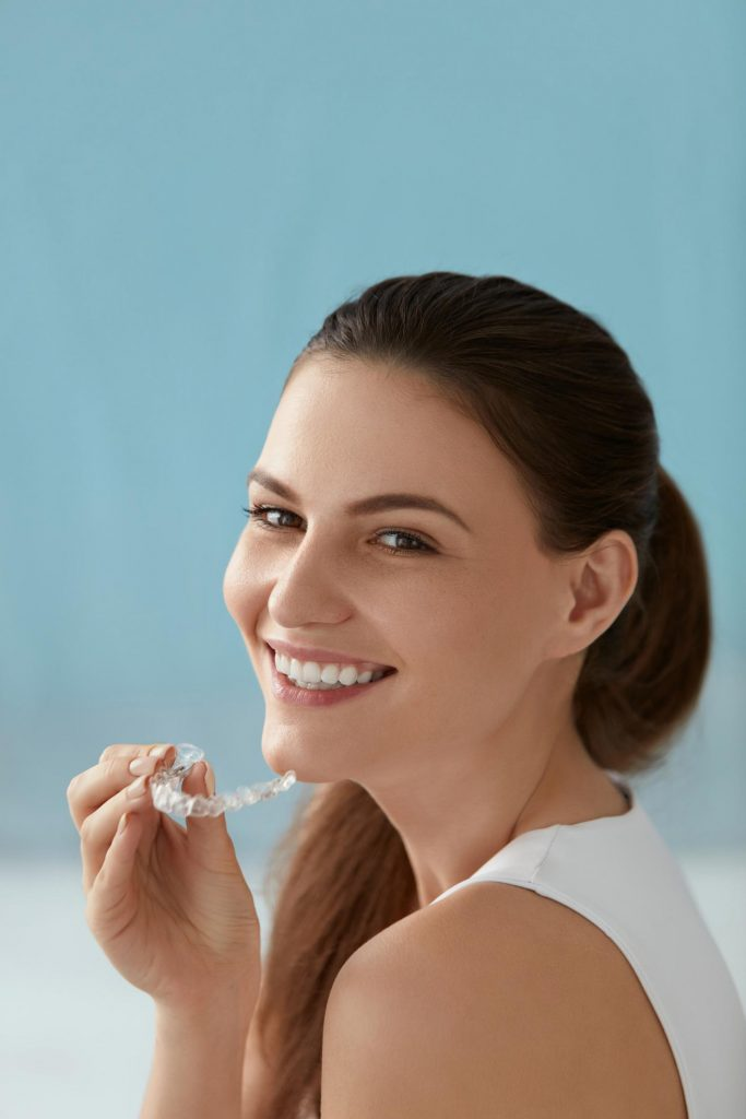 woman holding ClearCorrect invisible dental liners