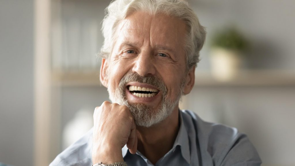smiling old man with implant-supported dentures