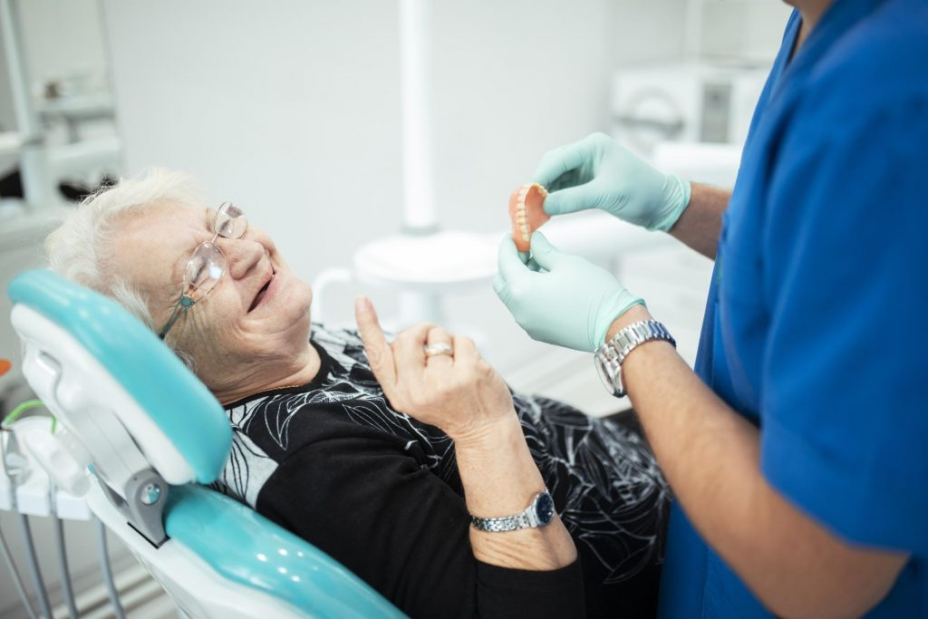 elderly woman getting dentures at a dental office